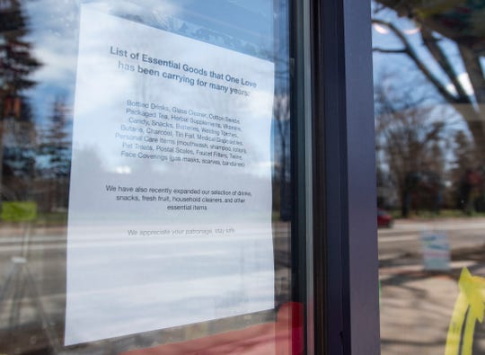 A paper detailing items for sale is taped to the storefront window for One Love as it remains open despite legal action from Larimer County officials to close the smoke shop amid a public health order during the coronavirus pandemic in Fort Collins, Colo. on Monday, April 6, 2020.