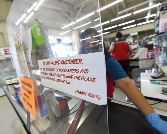Day Buy Day Supermarket cashiers work behind a protective glass in Piti, April 6, 2020.