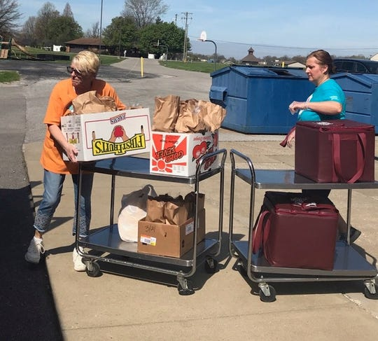 Debra Denton, left, and Lachele Mason load meals onto a Henderson County school bus for delivery, Monday, April 6, 2020, at East Heights Elementary School.