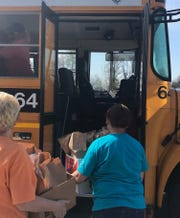 Henderson County school staff load a bus with meals to be dropped off to students (April 6, 2020).