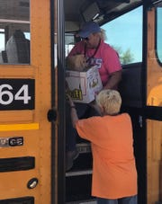 Debra Denton hands meals to Stacy Willingham, a bus driver for the Henderson County School District (April 6, 2020).