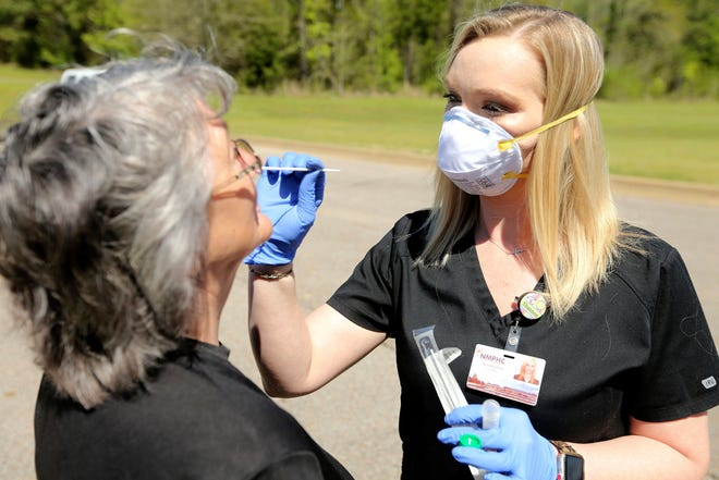 In this Thursday, April 2, 2020 photo, Shannon Bates, a nurse at Ripley Health Care Associates, demonstrates a COVID-19 test kit being given to Pattie Medlin, of Blue Mountain, in Ripley, Miss.