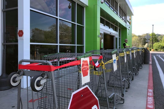 A barrier of grocery carts at the Wal-Mart Marketplace  on Monday, April 6, 2020, directs shoppers to enter and exit in a single file before entering the store.