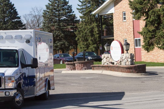 A Livingston County EMS ambulance pulls out of the driveway for Caretel Inns of Brighton Monday, April 6, 2020. Caretel Inns has begun accepting COVID-19 patients.