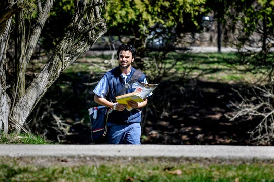 United State Postal Service carrier Travis Stanton delivers mail along his route on Monday, April 6, 2020, in East Lansing. Stanton said  delivering to businesses has been a little harder than usual since most are closed during coronavirus restrictions.