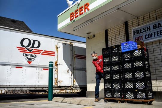 Quality Dairy delivery driver Randy Schalow takes a load of milk and eggs into the store at Harrison Road and Michigan Avenue on Monday, April 6, 2020, in East Lansing. Schalow said he's been keeping his distance from others while working his route since the coronavirus restrictions.