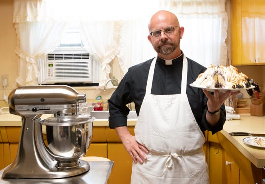 "Father Ben Bradshaw of St. Michael Catholic Church holds a homemade baked Alaska in the church's kitchen Monday, April 6, 2020. Bradshaw, a classically trained chef, has been hosting a cooking show for years called ""Soul Food Priest,"" which has taken on new meaning in the last few weeks as a way to connect with parishioners during a time when in-person church services have been canceled."