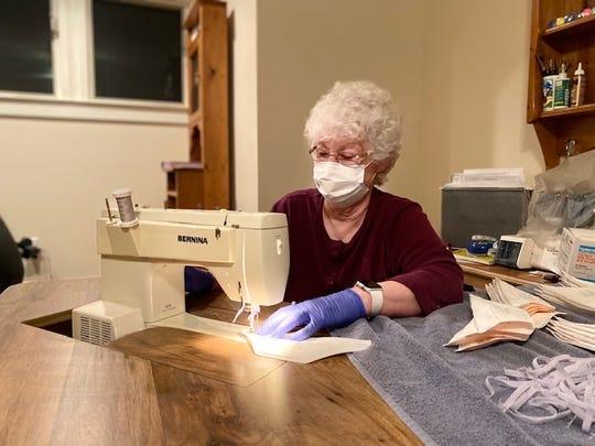 A volunteer works to sew elastic bands on N95 masks to return to Baptist Memorial Hospital