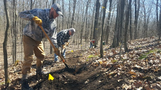 Volunteers with the Ice Age Trail Alliance work to build a new segment of the trail in Manitowoc County during a past trailbuilding event.