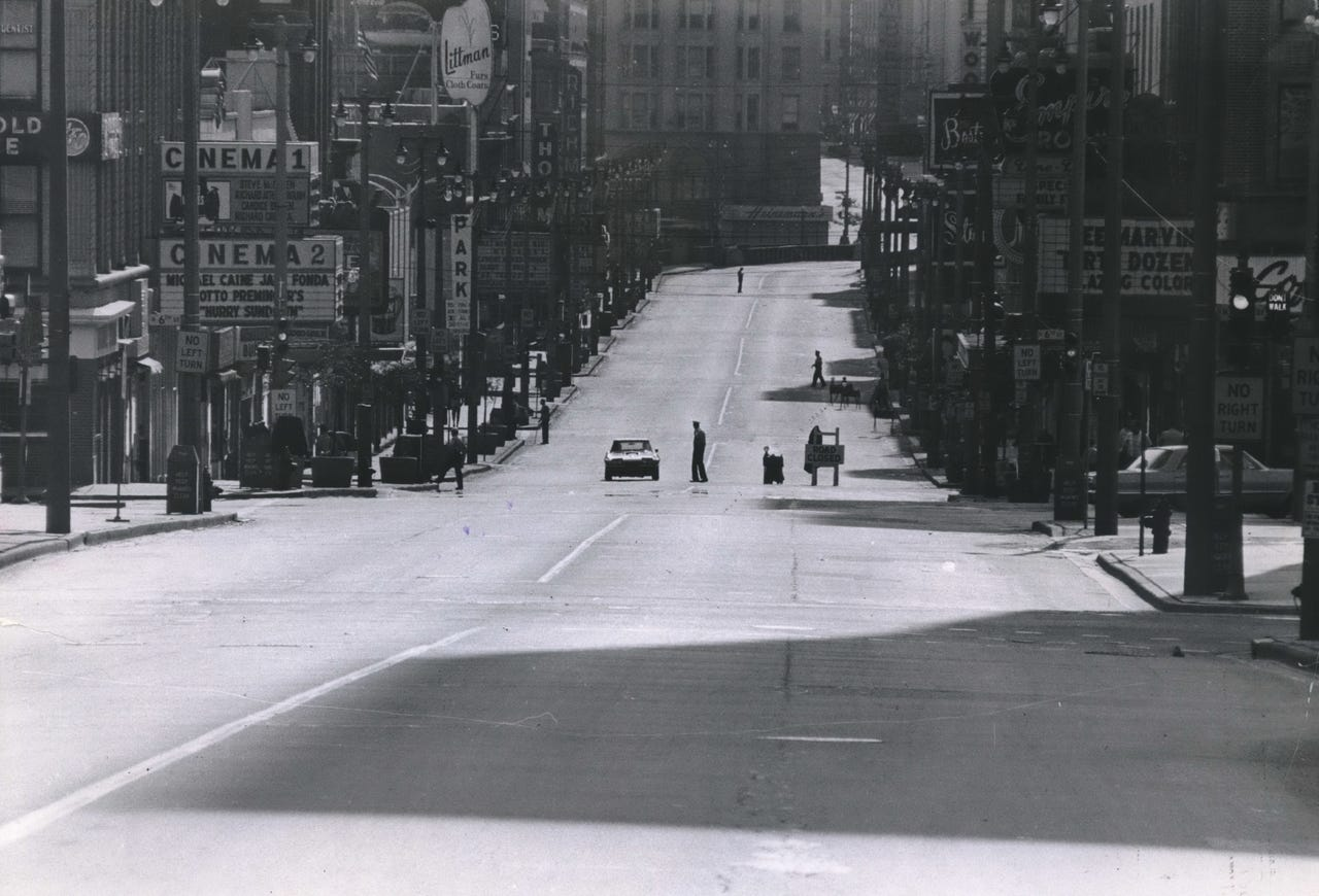 A police officer mans a roadblock in the middle of a deserted Wisconsin Avenue on the morning of July 31, 1967. That day, Mayor Henry Maier declared the city in a state of emergency and urged people to stay home following a riot on Milwaukee's north side. This photo was published in the Aug. 1, 1967, Milwaukee Journal.