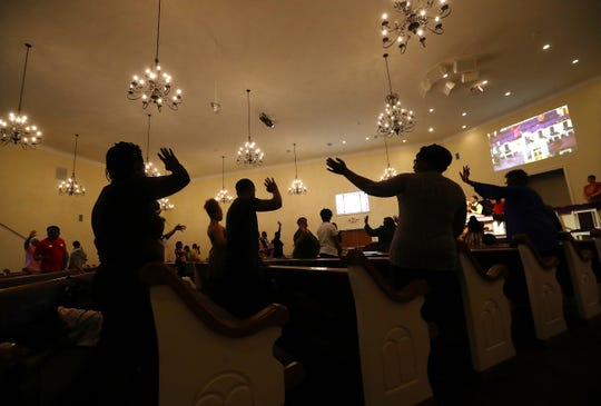 At the end of worship service, members wave goodbye to each other rather than hug or shake hands while as they practice social distancing in the pews at the Union Springs Baptist Church on Sunday, March 29 in Rutledge, Ga.