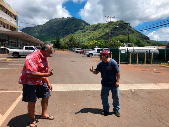 """Glen Kila, left, and Brad Suzuki, right, flash the Hawaii """"shaka"""" signs with their hands and give slight bows, demonstrating how they greet people using social distancing to curb the spread of coronavirus in Waianae, Hawaii."""