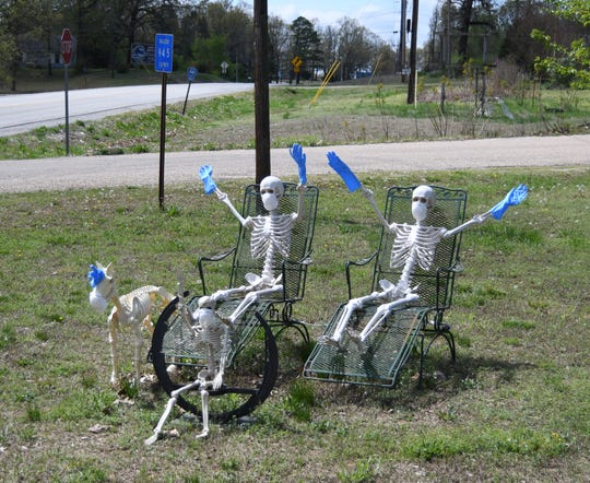 A group of skeletons wearing face masks and rubber gloves wave at motorists along Highway 178 on Sunday near Lakeview. The ongoing COVID-19 pandemic will keep Arkansas' school shuttered through the end of May, state officials announced Monday.