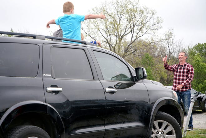 CommonGround Pastor Tom Dillingham gives a thumbs up to a car while a church goer gives a social distance appropriate hug during a drive-in church service at Admiral Twin Drive-In in Tulsa on Sunday, April 5.