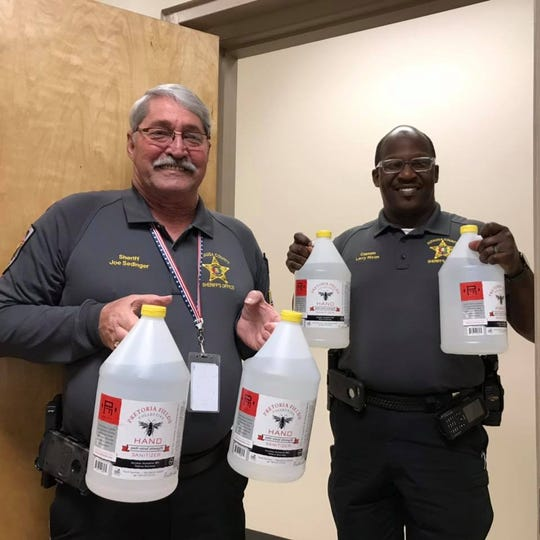 Autauga County Sheriff Joe Sedinger, left.  recently arranged a delivery of four gallons on hand sanitizer from Pretoria Fields Brewery in Albany, Ga.