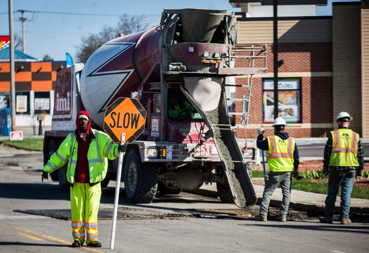 Construction crews work along Wheeling Avenue near McGalliard Road Monday, April 6, 2020.