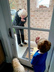 Mary Hance, AKA Ms. Cheap, blows a kiss to her grandson through the window of a door.