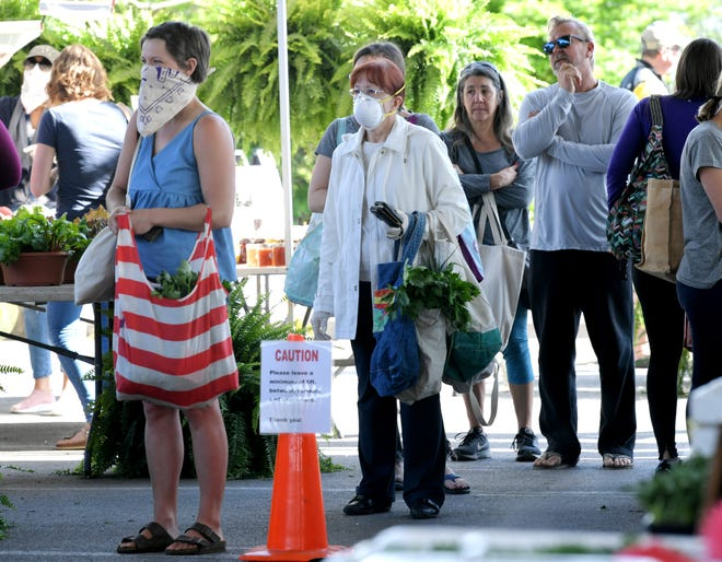 Some shoppers wear face masks while shopping at the Franklin Farmers Market on Saturday April 4, 2020.