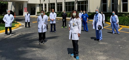 Dr. Maria Bendeck stands outside Naples Community Hospital with her colleagues who are fighting the coronavirus.