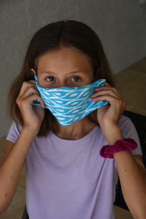 Bianca Fernandes, 12, of Marco Island models one of the completed masks. With her sewing school business shut down, Lauren Johnston of Marco Island set up a workshop session for young seamstresses to sew protective face masks to help medical personnel and others who need them.