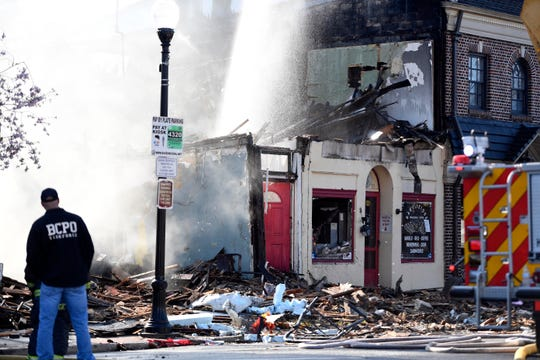 Ridgewood firefighters work on the smoking building the morning after a four-alarm fire ravaged Bagelicious and the surrounding apartments in downtown Ridgewood on Monday, April 6, 2020.