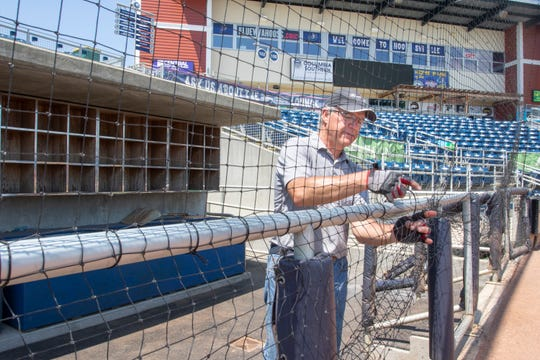 Owner Rob Huff, of C & H Baseball, works on installing netting from foul pole to foul pole at Blue Wahoos Stadium in downtown Pensacola on Monday, April 6, 2020.  The stadium is the first in professional baseball to install protective netting from pole to pole including in front of the team dugouts.
