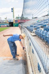 Elias Ruiz, of C & H Baseball, works on installing netting from foul pole to foul pole at Blue Wahoos Stadium in downtown Pensacola on Monday, April 6, 2020.  The stadium is the first in professional baseball to install protective netting from pole to pole including in front of the team dugouts.