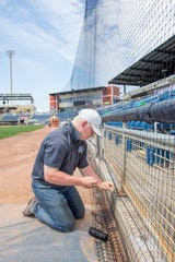 C & H Baseball employee Keegan Spengler, of Boise, Idaho, works on installing netting from foul pole to foul pole at Blue Wahoos Stadium in downtown Pensacola on Monday, April 6, 2020.  The stadium is the first in professional baseball to install protective netting from pole to pole including in front of the team dugouts.