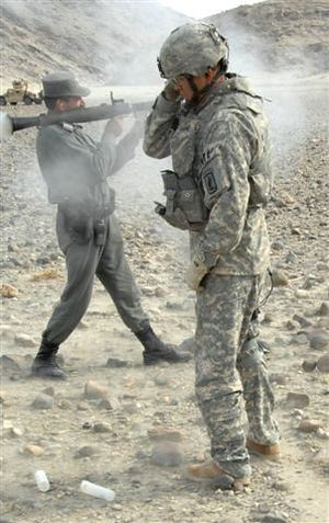 A U.S. Army Soldier from Headquarters and Headquarters Company, 173rd Special Troops Battalion covers his ear while coaching an Afghan National Police officer firing a rocket-propelled grenade launcher during a skills assessment mission on a range in Beshud, Afghanistan, Feb. 13, 2008.