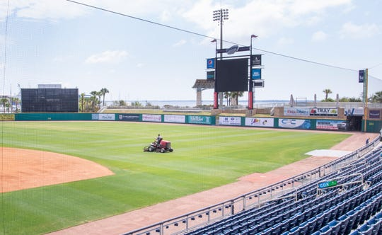 Head groundskeeper Dustin Hannah cuts the grass at Blue Wahoos Stadium in downtown Pensacola on Monday, April 6, 2020.