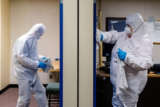 Two employees from Jarvis Property Restoration wear full PPE as they clean doors in the Port Huron Police station Sunday, April 5, 2020, in the Municipal Office Center in Port Hurojn.