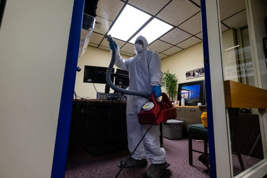 Carl Shy, lead technician for Jarvis Property Restoration, uses a ULV fogger to spray a disinfectant in an office in the Port Huron Police station Sunday, April 5, 2020, in the Municipal Office Center in Port Huron.