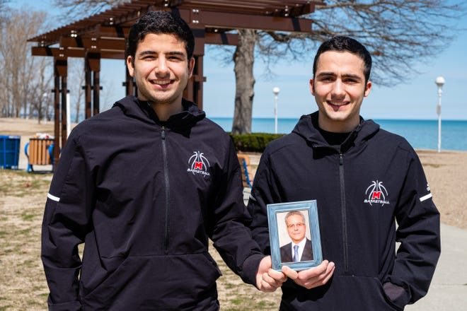 Brothers Peter and Paul Nasr hold a framed photograph of their father, Bassam Nasr, Monday, April 6, 2020, at Lakeside Beach in Port Huron. Bassam Nasr passed away last summer after his rehab following heart surgery took a bad turn.