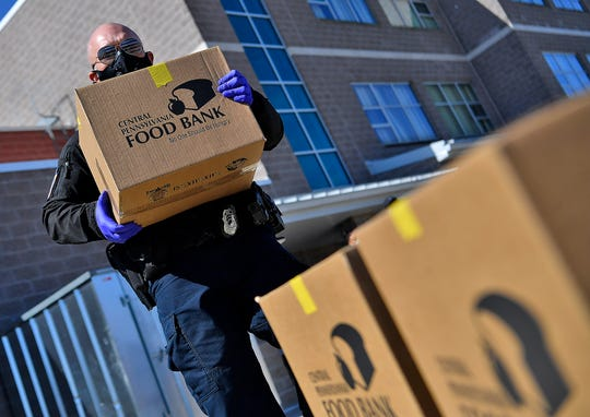 Officer Randolph Hernadez of the York City School Police stacks food boxes from the Central PA Food Bank at Ferguson Elementary School to be distributed to families of children in the York City School District, Monday, April 6, 2020. The school district has been providing free lunches for students for the past three weeks, the food box contains additional non-perishable meal items like, canned goods and pasta.John A. Pavoncello photo