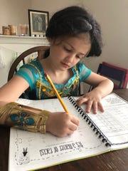 "Zoe, 6, dresses as Jasmine from ""Aladdin"" before doing her math homework."