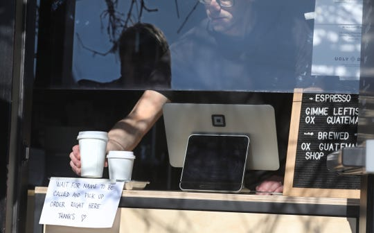 Rory Van Grol places an order of coffees in the takeout window at Ugly Duck Coffee in downtown Rochester on Monday, April 6, 2020. Ugly Duck has reopened, and turned its front door into a takeout window due to the coronavirus pandemic.