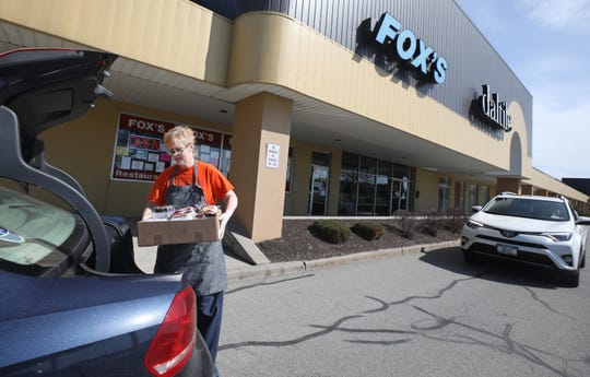 Amy Fox puts a called-in order into the trunk of a customers car outside of Fox's Deli in the Winton Plaza in Brighton on Monday, April 6, 2020.  The popular deli has reopened and is taking extra precautions with its curbside pickup service due to the coronavirus pandemic.