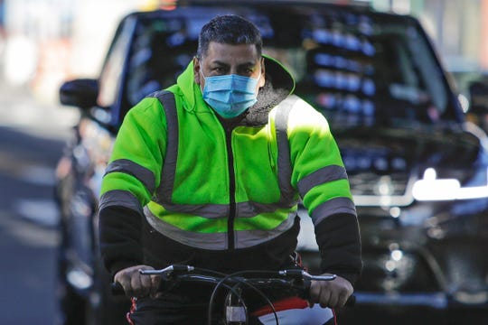 A man wears a mask as he bicycles down Roosevelt Avenue in Queens, N.Y., on April 4, 2020.
