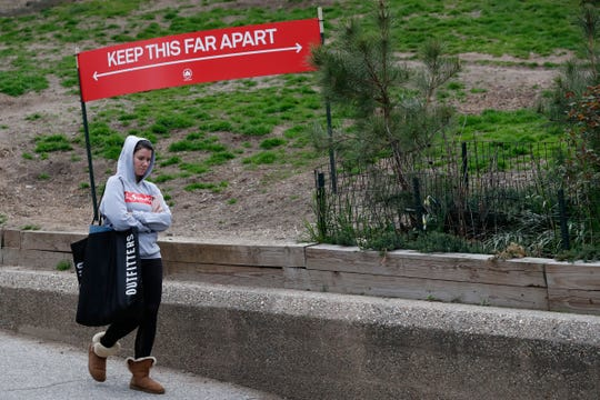 A woman passes a sign demonstrating the amount of space people should allow between each other to avoid contracting or spreading coronavirus as she leaves Fort Greene Park, Sunday, April 5, 2020, in the Brooklyn borough of New York.