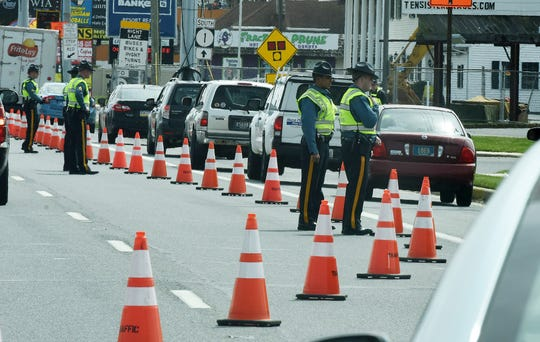 Delaware State Police man a checkpoint for the coronavirus on travel restrictions at on Coastal Highway near the entrance to Rehoboth Beach on Saturday, April 4, 2020.