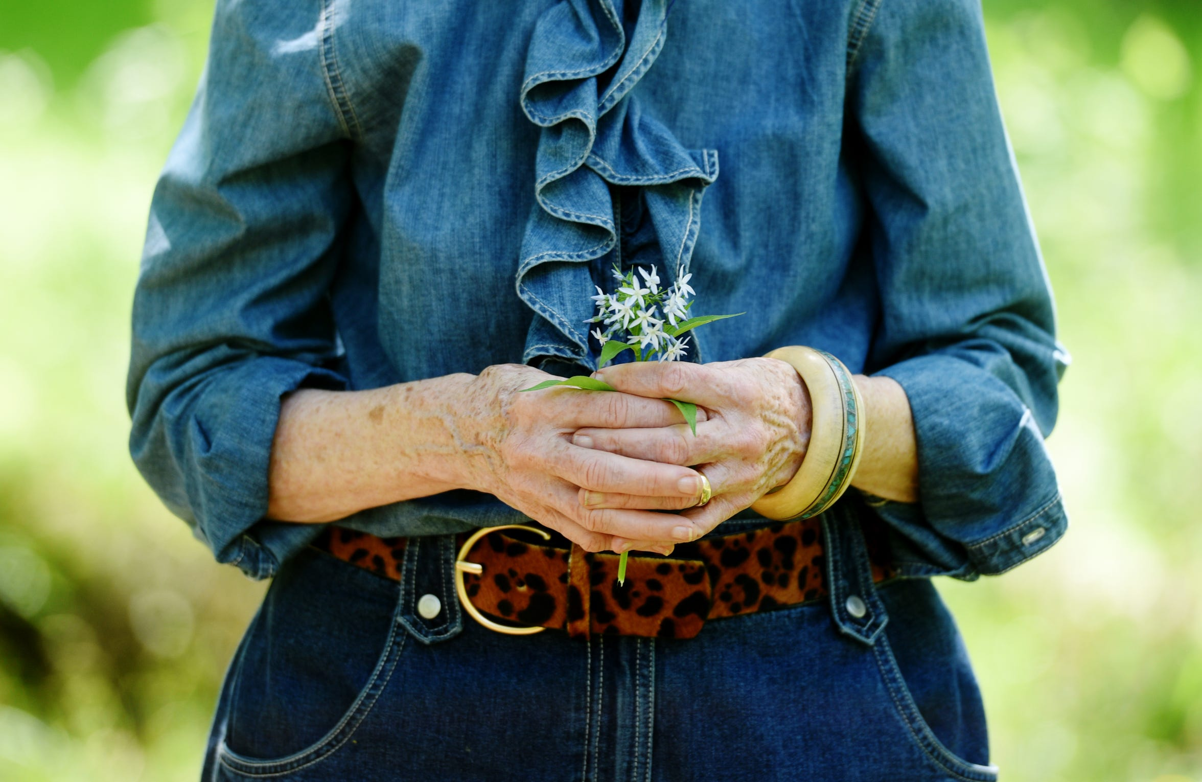 Maggie holds bouquet of native Blue Star Flower which is planted in the Pine Tree Garden.
