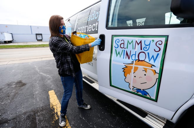 Shandy Miller, a kinship navigator with Foster Adopt Connect, loads a bag of groceries into a van for delivery to a Sammy's Window client on Monday. Sammy's Window, part of Foster Adopt Connect, has had to change the way it serves clients due to the coronavirus.