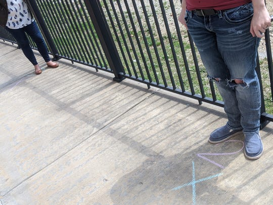 Rare Breed staff use sidewalk chalk to  mark where youths can stand as they wait in line for meals or to get in the building.