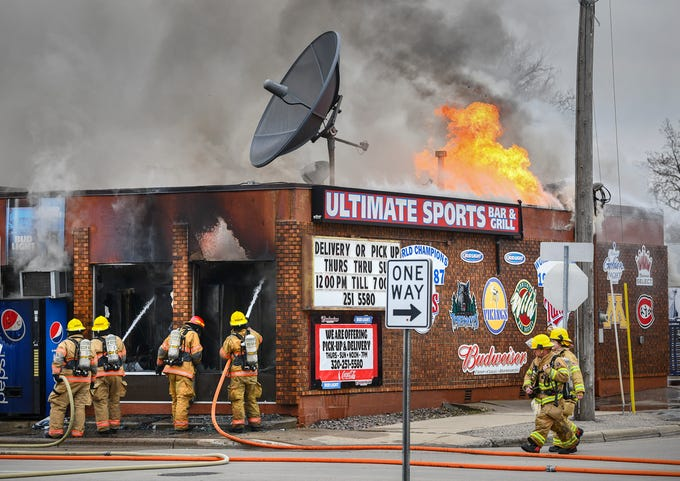 Firefighters battle a fire as flames leap from the roof at the Ultimate Sports Bar & Grill Monday, April 6, 2020, in Waite Park.