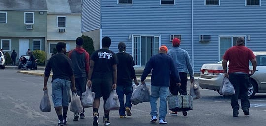 This group of men distributed food during a March 28 visit to Delsea Village apartments in Millville. Isaiah White set up the visit as part of his ministry through God's Location Church. Willie White, Jonathan Terrell Burks, Willie White Jr. , Raynard Gross, George Gibbs, Jaylen Mutts, and Malachi White are shown in this picture by Isaiah White.