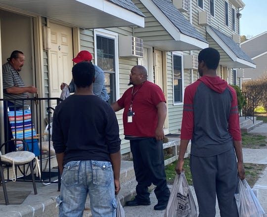 A resident of Delsea Village apartments in Millville accepts a bag of foodstuffs from a member of a faith-inspired group of men who distributed food to children and the elderly on March 28. The visit is part of a ministry by Isaiah White, pastor of God's Location Church. Left to right are group members Jaylen Mutts, Raynard Gross, George Gibbs, and Malachi White. SUBMITTED PHOTO: Isaiah White