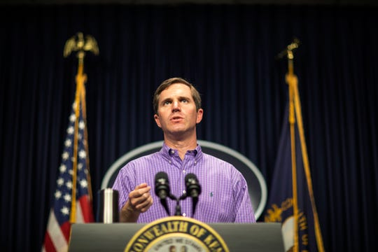 In this Sunday, March 29, 2020, photo, Kentucky Gov. Andy Beshear speaks during a news conference at the state Capitol in Frankfort, Ky., to provide an update on the novel coronavirus. Beshear announced a new order Monday, March 30 instructing Kentucky residents to avoid traveling to other states in another aggressive step to slow the spread of the new coronavirus. (Ryan C. Hermens/Lexington Herald-Leader via AP)