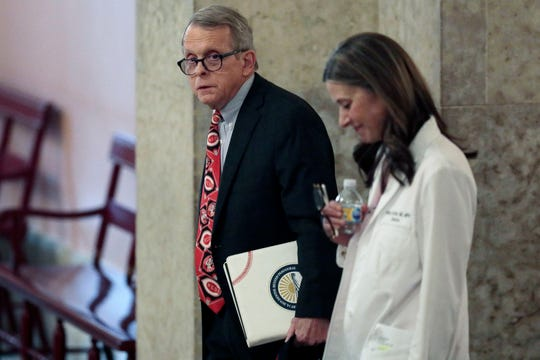 FILE - In this March 26, 2020, file photo Ohio Gov. Mike DeWine, left, and Dr. Amy Acton, director of the Ohio Department of Health, leave the State Room before their daily update on the states response to the ongoing COVID-19 pandemic at the Ohio Statehouse in Columbus, Ohio.