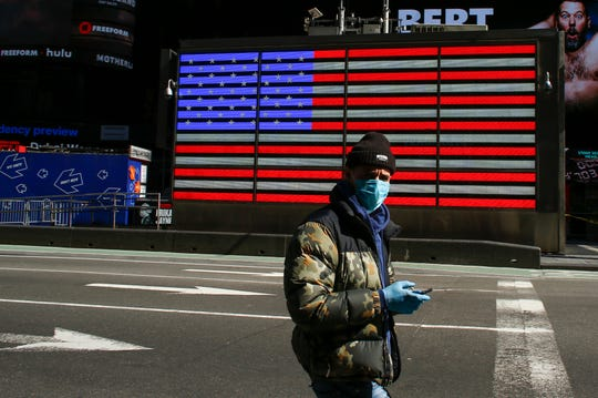 A man wears a face mask as he checks his phone in Times Square on March 22, 2020 in New York City.