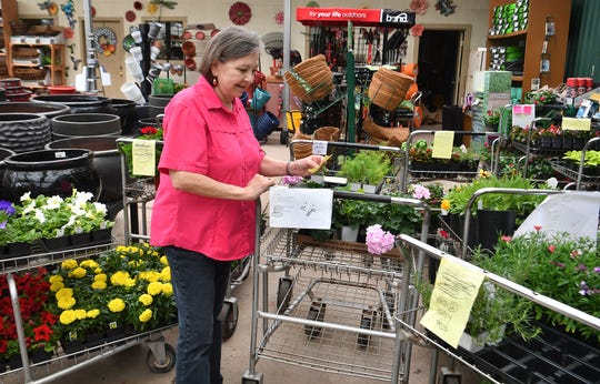 Katherine Smith, co-owner of Smith's Gardentown, checks customer orders waiting for curbside pickup while the business is closed to the public during the pandemic shutdown.